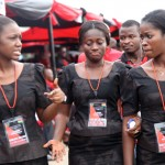 Usherettes dressed in black dresses walk passed guests at the funeral of President John Atta Mills