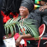 An elderly woman fans herself with an olive branch as she weeps at the funeral of President John Atta Mills in Accra, Ghana