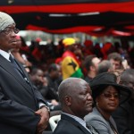A man finds solace from the heat with a handkerchief on his head at the funeral of President John Atta Mills