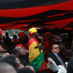 A man wear Ghana's flag as a cape at the funeral of President John Atta Mills in Accra Ghana