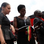 Two women dressed in black look at photos of President John Atta Mills handed out at his funeral at Independence Square