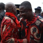 Two men dressed in Atta-Mills aschobi cotton exchange pleasantries at the funeral of President John Atta Mills in Accra