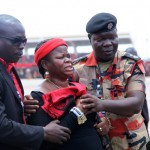Security personnel try to console a woman who weeping for President John Atta Mills at Independence Square in Accra, Ghana