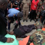 Security Personnel try to resuscitate a man who fainted at the funeral of President John Atta Mills in Accra, Ghana