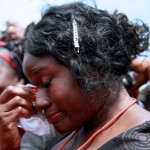 A woman weeps silently as President Mills' coffin is removed from the Independence Square in Accra, Ghana